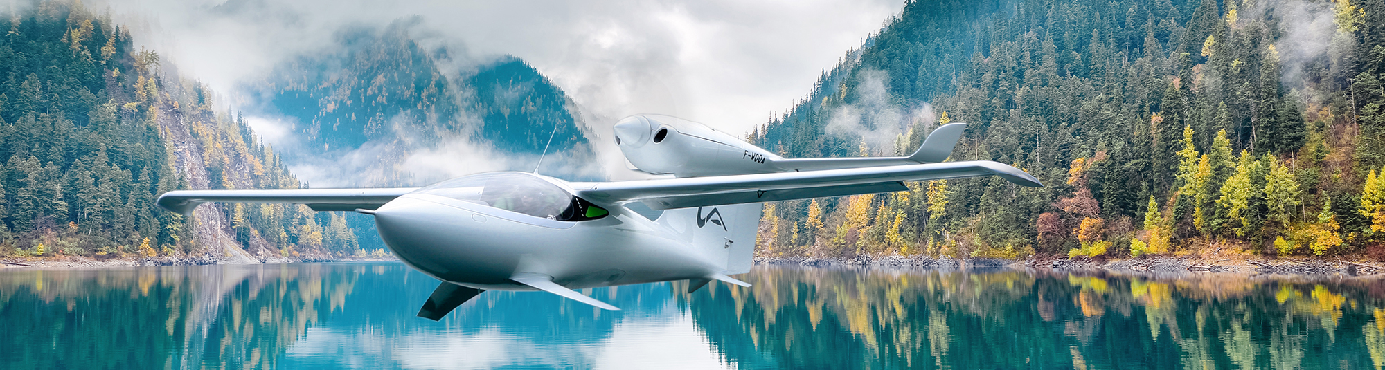 Akoya amphibious aircraft flying above lake and colorfull woods
