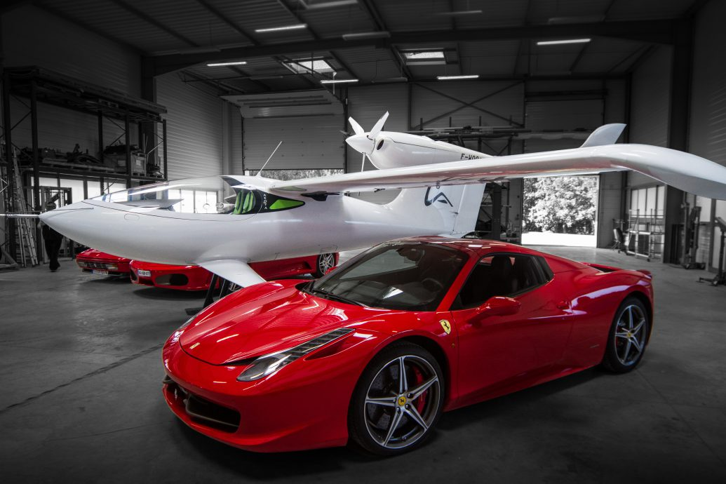 Private airplane in workshop with luxury cars