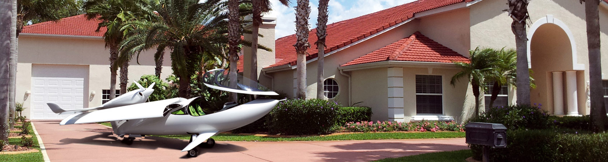 Seaplane with folding wings in front of a villa